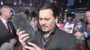 Johnny Depp coccola un microfono alla premiére londinese di Black Mass