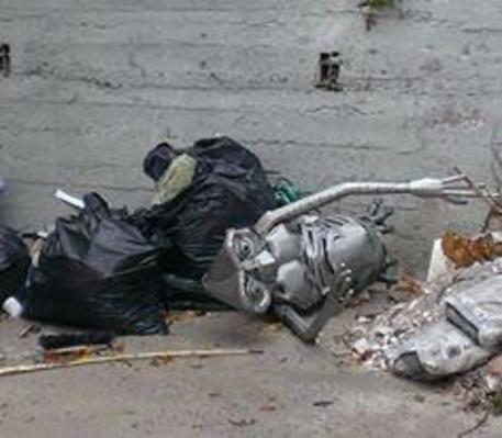 Statua ET tra rifiuti